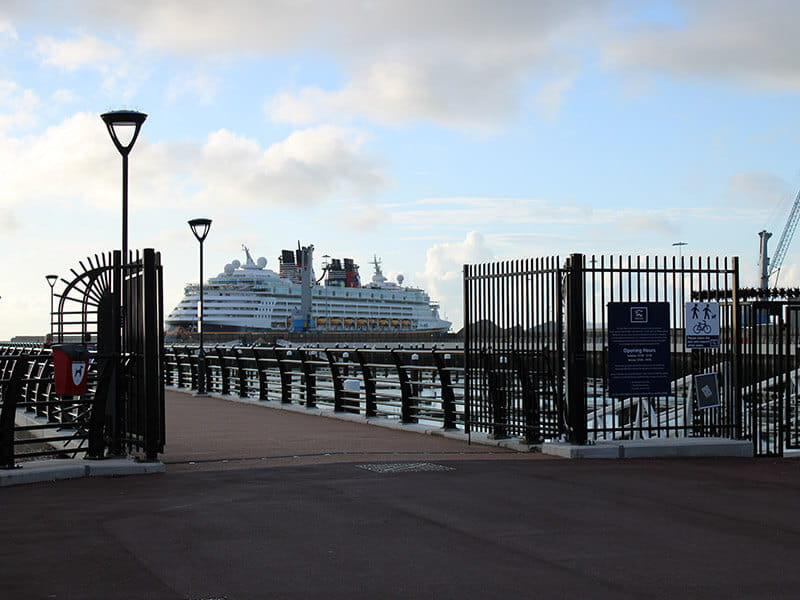 Double leaf vertical bar security gates at entrance to pier with ferry behind