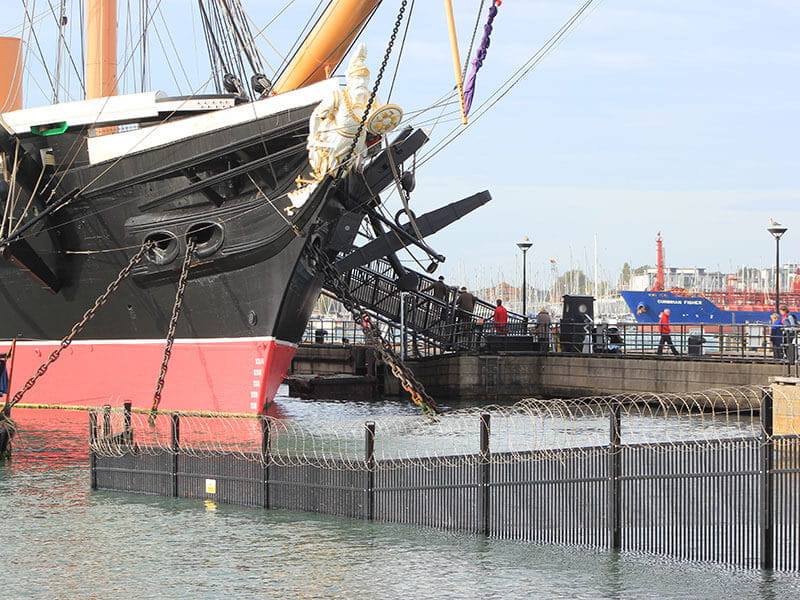 Black security fencing with barbed wire in sea at Portsmouth Historic Dockyard with historic ship behind
